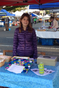 Addy at the farmer's market selling soap for St. Clare.